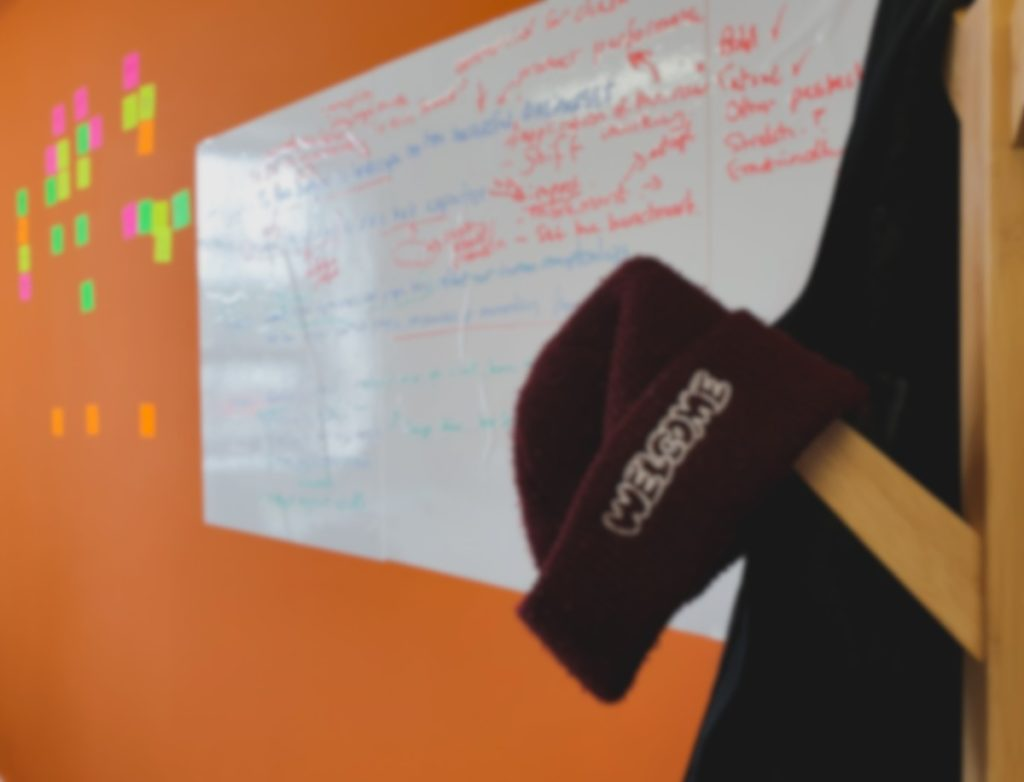 A maroon hat is placed on a coat rack with a whiteboard and some stickynotes in the background on an orange wall